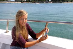 Happy blond girl with phone on the ship Stock Photo