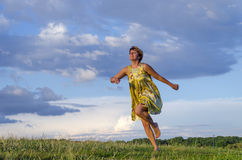 Happy blond girl running barefoot on grass in park on the green grass on a background cloudy sky Stock Image