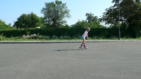 Happy blond girl of seven, rollerblading, a hot summer day. Slow motion stock footage
