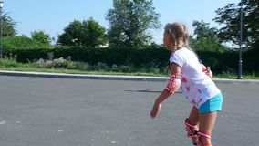 Happy blond girl of seven, rollerblading, a hot summer day. Slow motion stock video