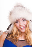 Happy blond girl in warm fur hat. Winter clothes. Fashion and beauty. Royalty Free Stock Image