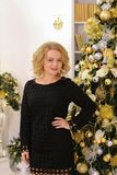 Happy blond girl widely smiling and posing against Christmas tre royalty free stock images