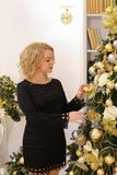 Happy blond girl widely smiling and posing against Christmas tre stock photo