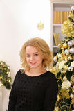 Happy blond girl widely smiling and posing against Christmas tre Stock Photos