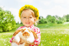 Happy blond girl with yellow flowers circlet. With rabbit in the park in summer Stock Image