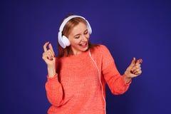 Happy blond in headphones dancing. In studio Stock Image