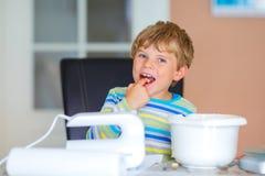 Happy blond kid boy baking cake indoors Royalty Free Stock Photography