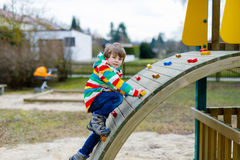 Happy blond kid boy having fun and climbing on outdoor playground. Funny joyful child smiling and making sports. Summer, spring and autumn leisure for active Royalty Free Stock Images