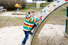 Happy blond kid boy having fun and climbing on outdoor playground. Funny joyful child smiling and making sports. Summer, spring and autumn leisure for active Stock Photo