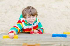 Happy blond kid boy having fun and climbing on outdoor playground. Funny joyful child smiling and making sports. Summer, spring and autumn leisure for active Royalty Free Stock Photography