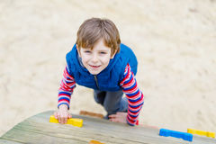 Happy blond kid boy having fun and climbing on outdoor playground. Funny joyful child smiling and romping on slide. Summer, spring and autumn leisure for Stock Image