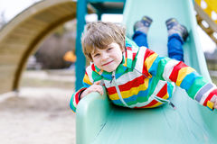 Happy blond kid boy having fun and sliding on outdoor playground. Funny joyful child smiling and climbing on slide. Summer, spring and autumn leisure for Royalty Free Stock Image