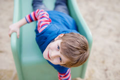 Happy blond kid boy having fun and sliding on outdoor playground. Funny joyful child smiling and climbing on slide. Summer, spring and autumn leisure for Stock Images