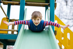 Happy blond kid boy having fun and sliding on outdoor playground. Funny joyful child smiling and climbing on slide. Summer, spring and autumn leisure for Royalty Free Stock Images