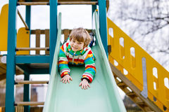 Happy blond kid boy having fun and sliding on outdoor playground. Funny joyful child smiling and climbing on slide. Summer, spring and autumn leisure for Stock Photography