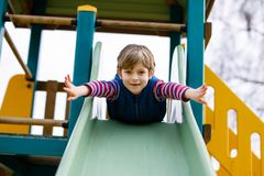 Happy blond kid boy having fun and sliding on outdoor playground. Funny joyful child smiling and climbing on slide. Summer, spring and autumn leisure for Royalty Free Stock Photos
