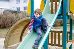 Happy blond kid boy having fun and sliding on outdoor playground. Funny joyful child smiling and climbing on slide. Summer, spring and autumn leisure for Stock Photo