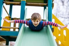 Happy blond kid boy having fun and sliding on outdoor playground. Funny joyful child smiling and climbing on slide. Summer, spring and autumn leisure for Royalty Free Stock Photography