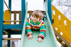 Happy blond kid boy having fun and sliding on outdoor playground. Funny joyful child smiling and climbing on slide. Summer, spring and autumn leisure for Stock Photos