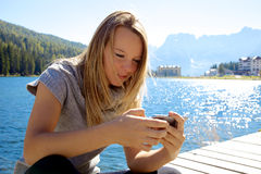 Happy blond lady texting message with cell phone Royalty Free Stock Photo