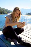 Happy blond lady texting message with cell phone medium shot Royalty Free Stock Images