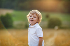 Happy blond little boy having fun on yellow hay field Stock Photos