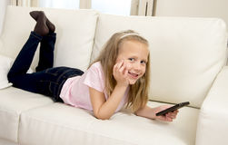 Happy blond little girl on home sofa using internet app on mobile phone royalty free stock photos