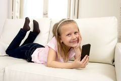 Happy blond little girl on home sofa using internet app on mobile phone Stock Images