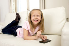 Happy blond little girl on home sofa using internet app on mobile phone Royalty Free Stock Images