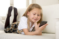 Happy blond little girl on home sofa using internet app on mobile phone Stock Image