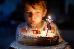 Happy blond little kid boy celebrating his birthday. Child blowing seven candles on homemade baked cake, indoor. Birthday party for school children royalty free stock photo