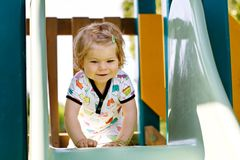 Happy blond little toddler girl having fun and sliding on outdoor playground. Positive funny baby child smiling. Summer leisure for small children, active Royalty Free Stock Photos