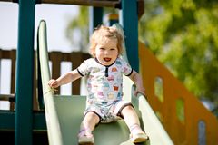 Happy blond little toddler girl having fun and sliding on outdoor playground. Positive funny baby child smiling. Summer leisure for small children, active Stock Image