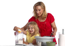 Happy blond mother and daughter baking Stock Photos