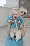 Happy blond mother holding her smiling baby Stock Photo