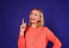 Happy blond pointing. Studio shot Royalty Free Stock Photography