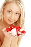 Happy blond in spa with red and white rose petals Royalty Free Stock Image