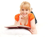 Happy blond student girl on bed reading book Stock Image