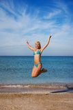 Happy blond svelte girl jumping at the beach Royalty Free Stock Image