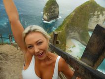 Happy blond tourist woman feeling free on the stunning view of beautiful sea cliff beach at viewpoint enjoying exotic Summer. Young attractive and happy blond royalty free stock photos