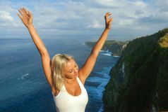 Happy blond tourist woman feeling free on the stunning view of beautiful sea cliff beach at viewpoint enjoying exotic Summer. Young attractive and happy blond royalty free stock images