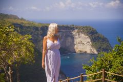 Happy blond tourist woman feeling free on the stunning view of beautiful sea cliff beach at viewpoint enjoying exotic Summer. Young attractive and happy blond stock image