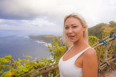 Happy blond tourist woman feeling free on the stunning view of beautiful sea cliff beach at viewpoint enjoying exotic Summer. Young attractive and happy blond royalty free stock photo