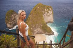 Happy blond tourist woman feeling free on the stunning view of beautiful sea cliff beach at viewpoint enjoying exotic Summer. Young attractive and happy blond stock photography