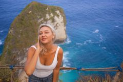 Happy blond tourist woman feeling free on the stunning view of beautiful sea cliff beach at viewpoint enjoying exotic Summer. Young attractive and happy blond stock images