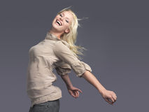 Happy Blond Woman With Arms Outstretched. Side view of a happy young blond woman standing with arms outstretched against gray background Royalty Free Stock Photography