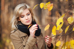 Happy blond woman in autumn forest Royalty Free Stock Photos