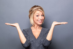 Happy blond woman displaying something equal on empty hands Stock Photography