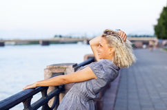 Happy blond woman in grey dress . Stock Images