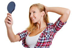 Happy blond woman looking into mirror. Happy blond woman looking into hand mirror and adjusting her hair Royalty Free Stock Photos